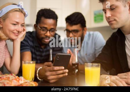 Quatre amis assis à table, de manger des pizzas, boivent des boissons alcoolisées, la lecture de message texte sur smartphone, l'essai de nouvelles application téléphone ensemble. Mult