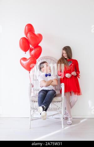 Fille et garçon avec des ballons rouges en forme de cœur Banque D'Images