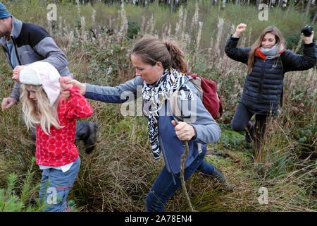 Les parents de la famille enfant tenant la main de marcher en terrain marécageux dans la campagne en automne dans Carmarthenshire Wales UK KATHY DEWITT Banque D'Images