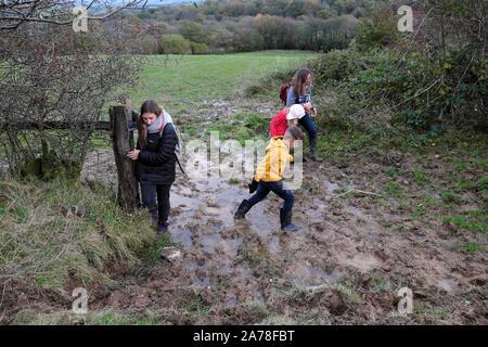 Les enfants de la famille marche à travers un champ boueux flaque dans la campagne à mi-saison à l'automne en Carmarthenshire Wales UK KATHY DEWITT Banque D'Images
