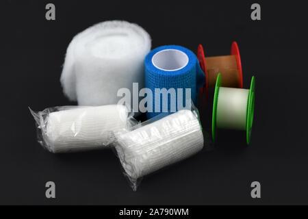 Pansements pour traitement des blessures comme les compresses et pansements auto-adhésif et adhésif sur fond sombre retour Banque D'Images
