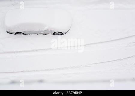 Vue de dessus sur silver car enterré dans la neige sur la route après blizzard. Beaucoup de neige dans la ville. Après une tempête de neige. Copier l'espace. Tempête de neige. L'espace pour le texte. Banque D'Images