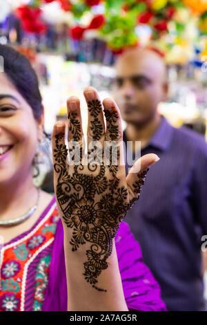 Heureux femme indienne montrant sa main fraîchement peintes au henné au marché dans Little India à Singapour. Banque D'Images