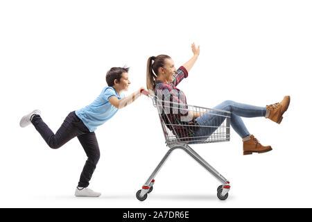 De toute la longueur un garçon poussant sa sœur adolescente dans un panier isolé sur fond blanc Banque D'Images