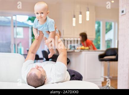 Concept de la famille, le père et l'enfant jouant sur le canapé, enfance heureuse. Une balle dans la cuisine. L'enfant dans ses bras, l'enfant lance jusqu'à l'ince Banque D'Images