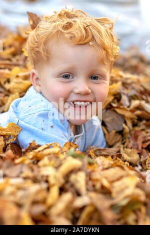 Portrait of happy little red hair garçon couché au milieu de feuilles aux couleurs automnales