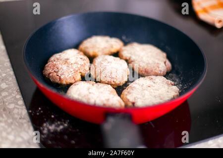 Des escalopes dans poêle cuisson sur plaque à induction. Close up.