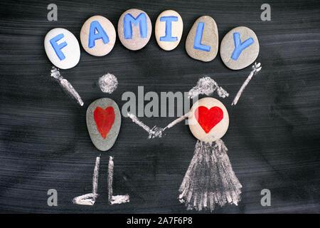 Cailloux avec coeurs rouges à l'intérieur de dessin à la craie de l'homme et de la femme et de la famille des lettres sur galets sur tableau noir. Close-up. Banque D'Images