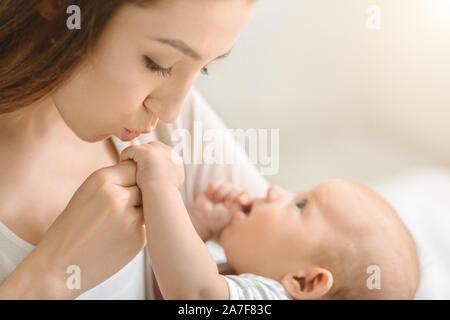 Mère embrassant son précieux bébé petite main Banque D'Images