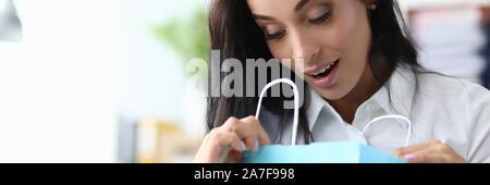 Femme Surpised loock en bleu sac de papier contre