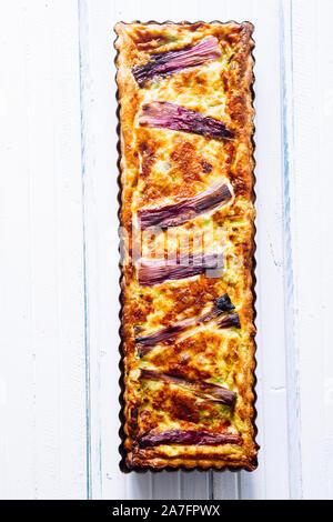 Cake salé à l'oignon de printemps rayures, à la fontina ,des oeufs, de la crème, et des saucisses, violet stripses au sommet, de formes rectangulaires sur fond sombre Banque D'Images