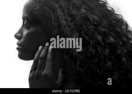 Portrait de profil d'une belle jeune femme africaine avec d'épais cheveux bouclés toucher doucement son visage, sur fond blanc
