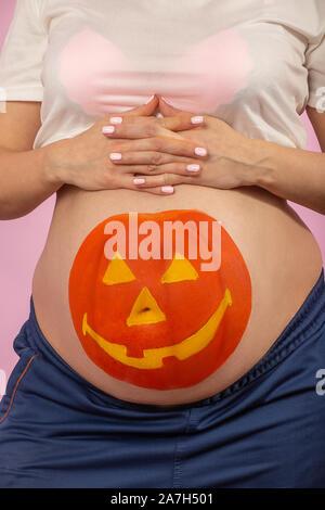 Jeune femme enceinte avec halloween citrouille peinte sur son estomac closeup portrait Banque D'Images