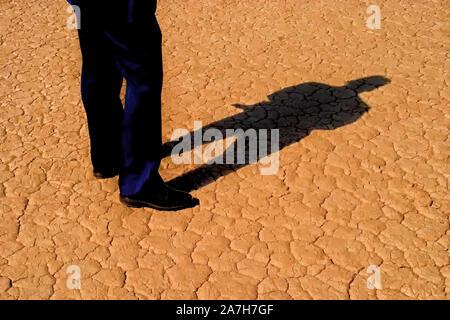Les jambes de l'homme dans les affaires et un corps entier sur ombre terre désert craquelé Banque D'Images