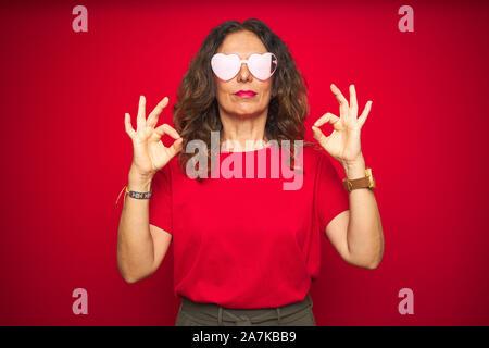 L'âge moyen senior woman wearing mignon lunettes en forme de coeur rouge sur fond isolé vous détendre et souriant avec les yeux fermé faisant geste de méditation wit Banque D'Images