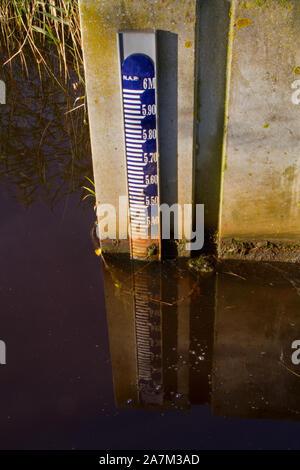 Jauge de niveau d'eau bleu sur un mur de béton, reflétée dans l'eau Banque D'Images
