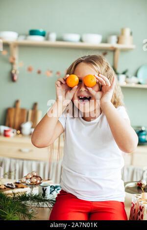 Portrait d'une petite fille aux mandarines dans ses yeux, noël, cuisine, chambre confortable
