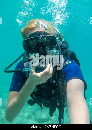 Young caucasian woman vêtus de l'équipement de plongée sous-marine natation en mer ionienne Corfou , Grèce .plongée à locations Women making selfies Banque D'Images