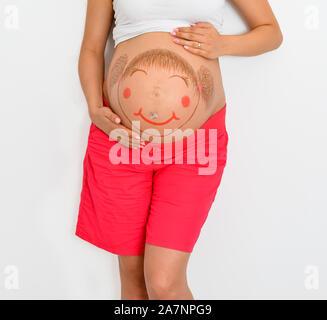 Close-up portrait portrait de jeunes femmes enceintes blanc peint avec smiley heureux d'une petite fille sur le ventre standing against white backg Banque D'Images