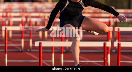 Un high school girl porte un uniforme noir lors de l'exécution dans une course de haies sur un circuit et sur le terrain de la concurrence. Banque D'Images