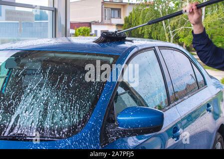 En utilisant une brosse pour laver une voiture sur une installation de lavage de voiture sur journée ensoleillée.lave-auto manuel avec de l'eau sous pression en lavage de voiture à l'extérieur.bleu manuel voiture Banque D'Images