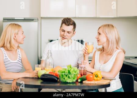 Jeunes amis avoir partie à la maison, manger de la pizza, boire du jus de fruit et de sourire. La compagnie des jeunes gens joyeux se reposant dans une cuisine. Friendshi Banque D'Images