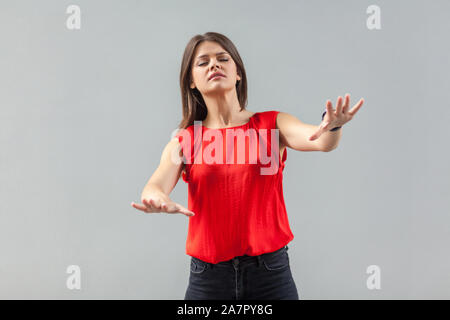 Aveuglement! Les meilleurs prix pour votre portrait de belle brune jeune femme en chemise rouge debout avec les yeux fermés et d'essayer de toucher ou de trouver quelque chose. piscine, studio Banque D'Images