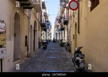 L'une des nombreuses rues étroites colorées dans la ville de Cefalú sur l'île de la Sicile, Italie. Banque D'Images