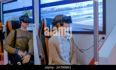 Jeune femme et l'homme à l'aide de lunettes de réalité virtuelle et à la recherche autour de: concept VR Banque D'Images