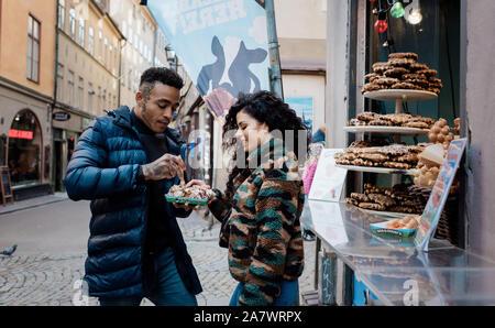 Couple partageant la nourriture dans la rue, sourire et rire ensemble Banque D'Images