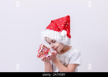 Little Boy in santa hat avec gingerbread house sur fond blanc. La carte de bonne année. L'attente de la maison de vacances Banque D'Images