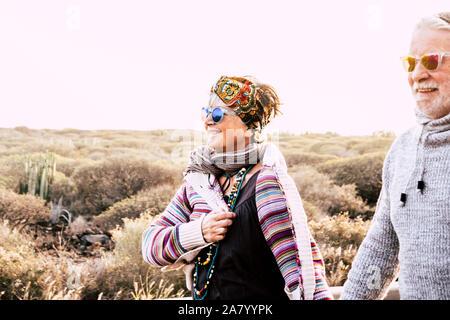 Senior active happy cheerful couple marcher ensemble dans l'activité de loisirs de plein air avec blanc ciel lumineux en arrière-plan et la nature. - L'amour ensemble pour toujours