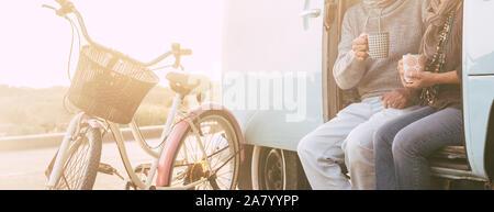 Méconnaissable des profils senior couple sitting on un vieux millésime van ensemble boire le thé ou café - vieux vélos et de la lumière du soleil en arrière-plan - concept de l
