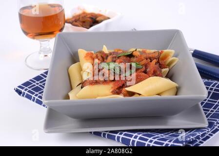 Pâtes Pennoni sauce avec des moules sur la plaque à fond blanc