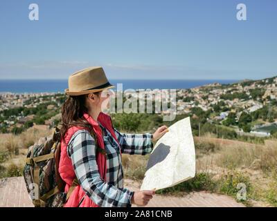 Jeune femme touriste dans un chapeau avec une carte dans les mains sur la nature Banque D'Images