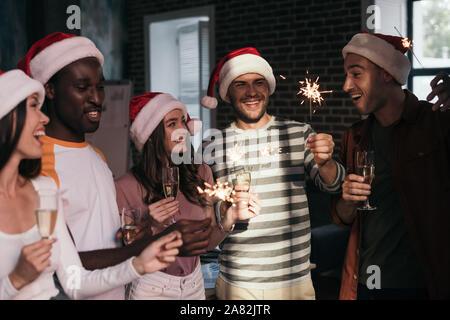 Heureux, les jeunes gens d'affaires à santa hats holding cierges et verres de champagne Banque D'Images