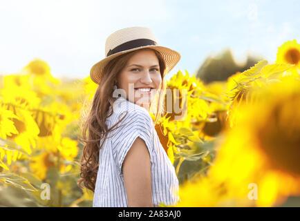 Belle jeune femme dans champ de tournesol sur journée d'été Banque D'Images