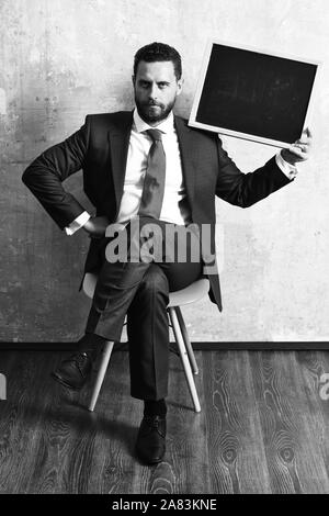 Marketing. serious businessman holding a blackboard Banque D'Images