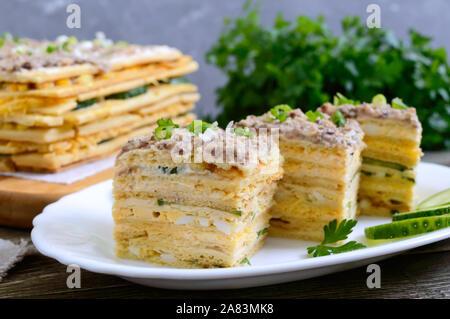 Layer Cake avec des oeufs, du fromage, des oignons verts, du poisson en conserve, la mayonnaise sur une plaque blanche sur une table en bois. Apéritif de fête. Close-up. Banque D'Images