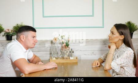 Jeune homme inquiet taps doigts sur table en bois assis en face de belle femme sérieuse en lumière confortable cafe