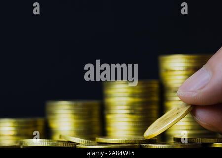 L'épargne, l'investissement de l'argent, gagner de l'argent pour l'avenir, la gestion de patrimoine financier concept. Un homme hand holding coin sur l'augmentation des pièces empilées illustre Fu. Banque D'Images