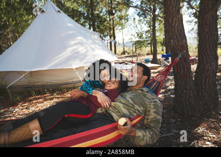 Heureux, insouciant family relaxing in hammock de camping dans les bois Banque D'Images