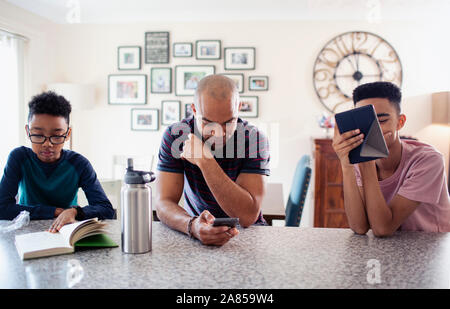 Père et fils, smart phone and reading book in kitchen
