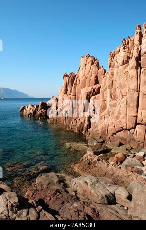 Les touristes explorant le Rocce rosse / Plage des Roches Rouges de porphyre sur la formation de la Sardaigne côte à côte en Ogliastra, Arbatax Tortolì, Sardaigne, Italie Banque D'Images