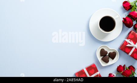 Concept de la Saint-Valentin. Boîtes cadeaux enveloppés de papier rouge, fleurs roses, tasse de café et de confiseries au chocolat en forme de coeur sur fond bleu avec copie espace Banque D'Images