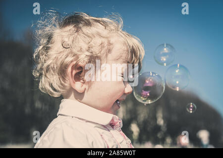 Belle petite fille cheveux brun, a fun heureux visage souriant, jolie yeux, cheveux courts, jouer et attraper des bulles de savon en été la nature, habillé Banque D'Images