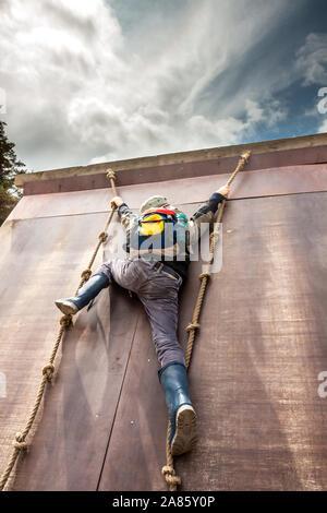 Jeune garçon de wellys escalade un mur avec des cordes.