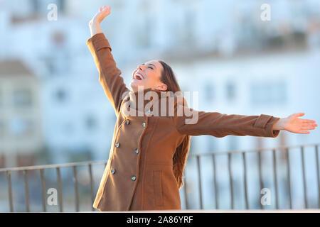 Veste femme portant excité raising arms en hiver dans un balcon