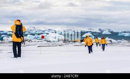 Tourisme en Antarctique, en tant que touristes portant des parkas correspondant à pied sur la neige, avec vue sur la mer et les icebergs dans l'arrière-plan. Banque D'Images