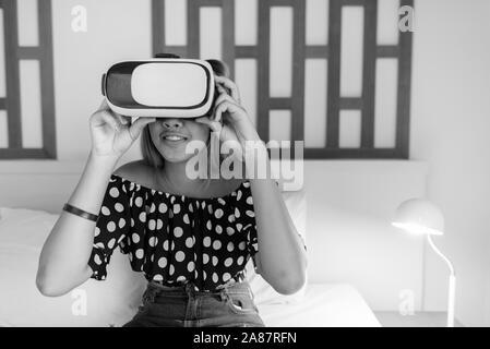 Young Asian teenage girl using casque de réalité virtuelle à la maison Banque D'Images